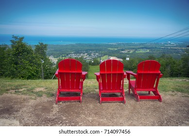 View of 3 red muskoka chairs at Blue Mountain resort and village during the summer in Collingwood, Ontario