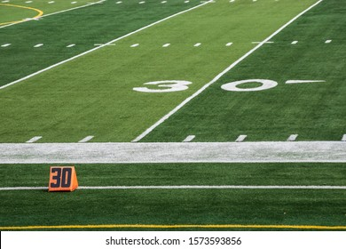 View of 30 yard line markings on American football field with artificial turf