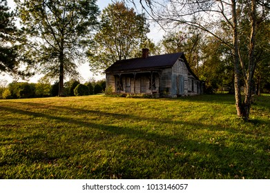 A view of an abandoned house with barren clapboard siding in the late evening in central Kentucky.