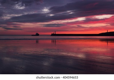 A view of Aberdeen beach at dawn showing a vessel approaching the harbour entrance. Aberdeen Scotland.