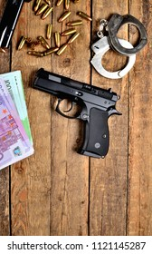 View from above of 9mm handgun pistol - handgun, handcuffs, bullets, euro banknotes and magazine on old wooden table - vertical photo
