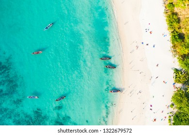 View from above, aerial view of a beautiful tropical beach with white sand and turquoise clear water, longtail boats and people sunbathing, Freedom beach, Phuket, Thailand.