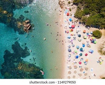 View from above, aerial view of an emerald and transparent Mediterranean sea with a white beach full of colored beach umbrellas and tourists who relax and swim. Costa Smeralda, Sardinia, Italy.