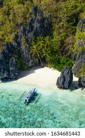 View from above, aerial view the Entalula Beach, a white sand beach surrounded by rocky formations and bathed by a crystal clear sea. Entalula island, Bacuit Bay, El Nido, Palawan, Philippines.
