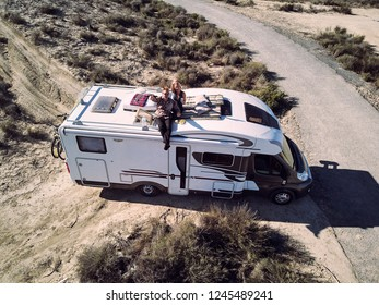 View from above, aerial photo recreational vehicle motor home trailer near empty road. Married couple sitting at car roof and  waving hands sitting at sunbed mattress feels happy having romantic date