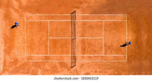 View from above, aerial view of two people playing tennis on a clay court during the Coronavirus (Covid-19) outbreak.