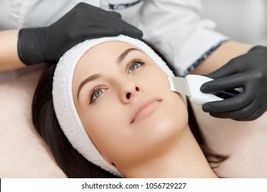View from above of beautiful woman with smooth skin getting facial in modern beauty salon. Hands of beautician, in black gloves, doing ultrasonic cleaning with help of special apparatus.