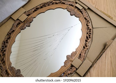 View from above of broken mirror vintage wooden frame with a damaged glass surface - bad-luck concept
