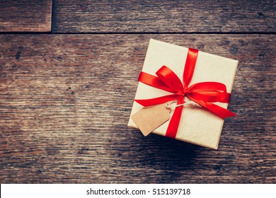 View above brown gift box and red ribbon with tag on wood background with space.