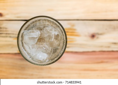 View above clean water with clear ice. Clear glass on wooden table