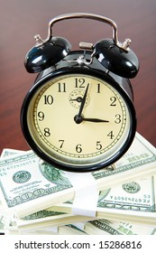 View from above of clock upon heap of dollars on the surface of table