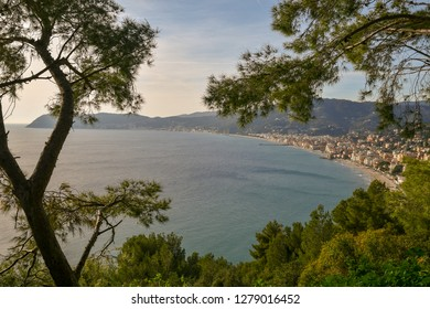 View from above of the coastal city of Alassio with Capo Mele on the horizon, Liguria, Italy