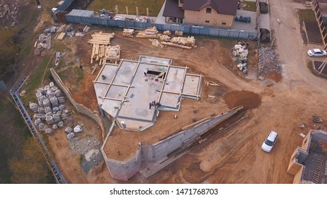 View from above of the construction site in progress, workers building new house or workshop and construction materials wooden boards, rocks, bricks . Clip. Process of new building construction.