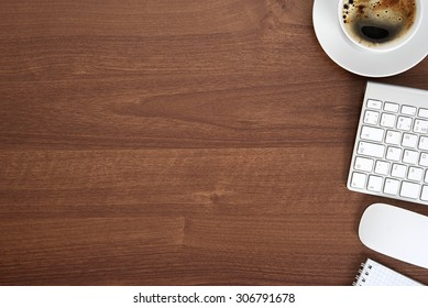 View from above with copy space, office table with notepad, keyboard and coffee cup.