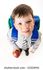 View from above of cute schoolboy with backpack and apple looking at camera