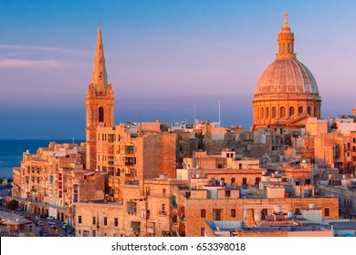 View from above of the domes of churches and roofs at beautiful sunset with churches of Our Lady of Mount Carmel and St. Paul's Anglican Pro-Cathedral, Valletta, Capital city of Malta