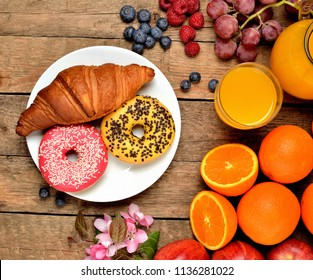 View from above of donuts, croissant, orange juice, blueberries, raspberries, apples and spring flowers - sweet breakfast on wooden table