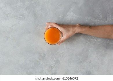 View from above of female hand holding glass of juice