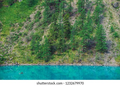 View above fisherman in boat on azure water of mountain lake. Fishing on highlands. Giant mountainside with forest in sunlight. Atmospheric minimalist beautiful landscape of nature in sunny day.
