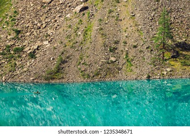 View above fisherman in boat on azure water of mountain lake. Fishing on highlands. Giant mountainside with conifer trees in sunlight. Atmospheric minimalist beautiful landscape of nature in sunny day