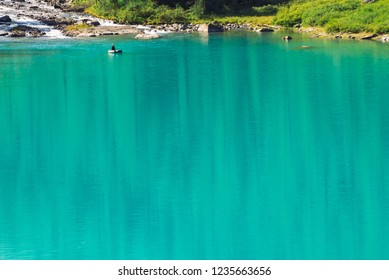 View above fisherman in boat on azure water of mountain lake. Fishing on highlands. Mountainside with rich vegetation in sunlight. Atmospheric minimalist beautiful landscape of nature in sunny day