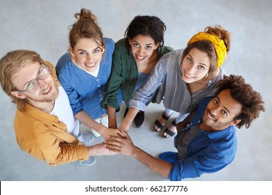 View from above of five multiracial people standing together stacking their hands looking happily symbolyzing their friendship and support. International fellowship. Mixed race people community