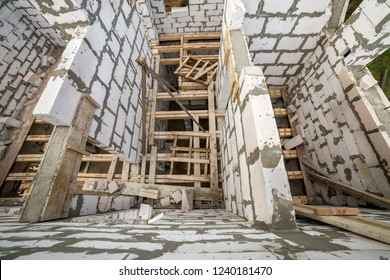 View from above of future multi stored cottage energy saving walls of large white hollow foam insulation blocks and temporary wooden scaffolding frame. Construction masonry, modern technology concept.