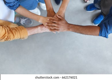View from above of group of people keeping their hands in pile expressing social friendship, unity, agreement and support. Five people of different sexes collaborating showing their strength