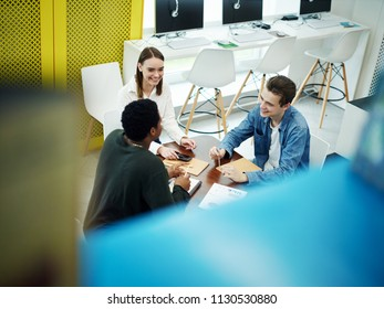 View from above of group of young multiethnic friends sitting at table with notebooks and smiling in library