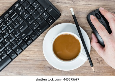 View from above of hand holding mouse and pencil on coffee cup and keyboard on the wooden office desk table