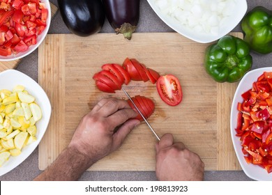 View from above of the hands of a man preparing vegetables in the kitchen slicing tomatoes on a wooden board surrounded by diced zucchini, onion, tomato and whole fresh green bell peppers and eggplant