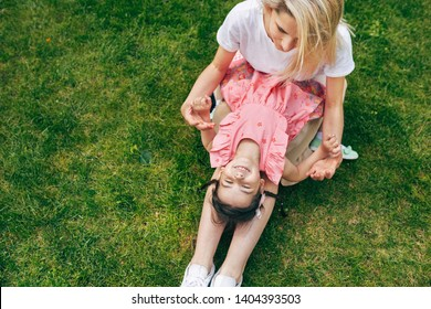 View from above of happy child playing with mother outdoor sitting on green grass. Happy woman and her child playing together in the park. Happy love emotion. Happy Mothers day. Motherhood, childhood