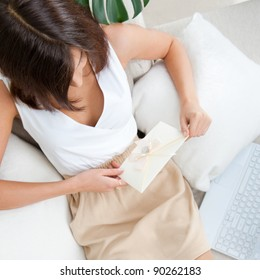 View from above of happy girl lying on sofa holding letter with valentine greeting card from her couple. She is happy reading lovely text. Tasty cakes, plant and laptop near her