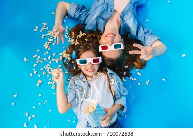 View from above happy mother and daughter laying on floor, having fun with popcorn isolated on blue background. Fashionable family in jeans clothes, wearing 3D glasses, expressing happiness