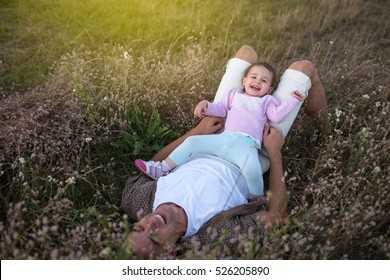 View from above of happy young father sitting face to his cute happy toddler girl playing and laughing on the grass. Happy father with his baby girl walking on the meadow.