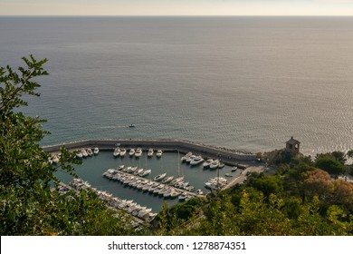View from above of the harbor of Alassio, with docked boats and the Cappelletta (little chapel), Liguria, Italy