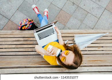 View from above hipster student woman tourist in yellow glasses drinking takeway coffee and sitting on the wooden bench. Teen girl in yellow eyeglasses with laptop, backpack and umbrella.