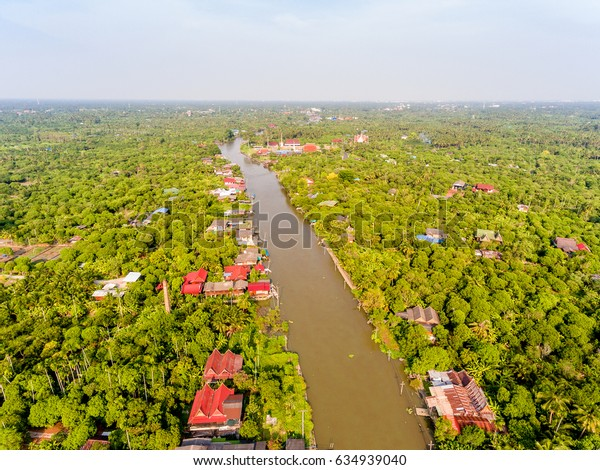 The view from above of houses, Buddhist temple, and orchards along a canal in Samut Songkram province of Thailand