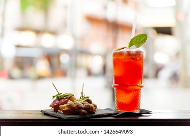 view from above of italian aperitivo with food and spritz cocktail with orange slice on bar top with natural light