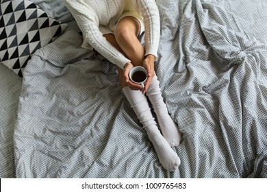 view from above of legs in socks, woman sitting on bed in morning, drinking coffee in cup, breakfast, cozy, comfortable at home, happy mood, legs details, stylish sheets, winter style, sexy