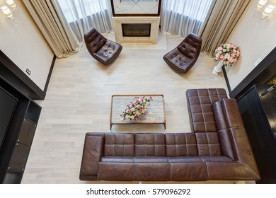 View from above of  living room with fireplace and big mirror under, leather sofa and armchairs around, glasses table with flowers on table.