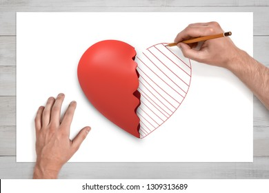 View from above of man's hands on a desk drawing with a pencil the second half of the broken red heart lying on a white sheet of paper. Love hurts. How to deal with feelings. Mend broken heart.