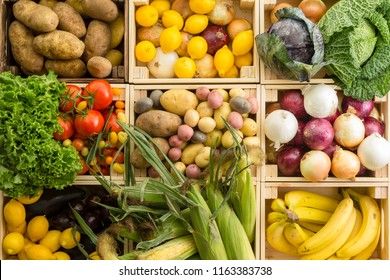 View from above nine rectangular wood boxes filled with assorted vegetables including potatoes and lemons