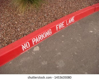 "View From Above Of ""No Parking Fire Lane"" Curb Sign"