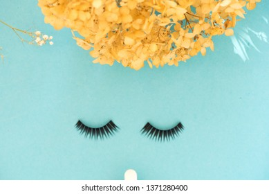 The view from above on the abstract face of a woman with eyelashes, hair and nose on a blue background. Cosmetics