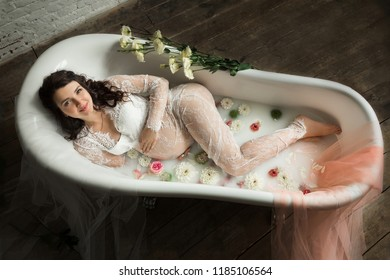 View from above on a beautiful pregnant woman in milk bath with flovers.