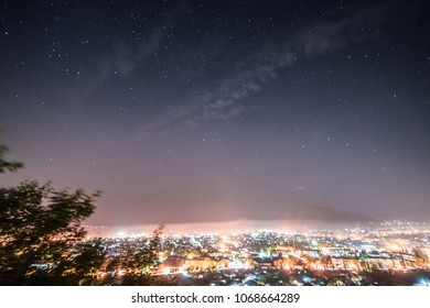 a view from above on a big city at the foot of the mountains, many glowing lights and lanterns under the night sky