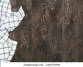 View from above on brown wooden table with linen kitchen towel or textile napkin. Blue tablecloth on dark brown wood tabletop. Copy space for text. Can use as mock up for design