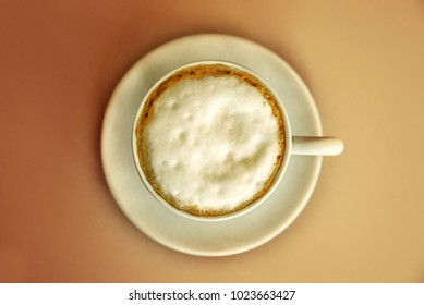 View from above on cup of capuccino. Coffe on the table. Top view of a cup of coffee
