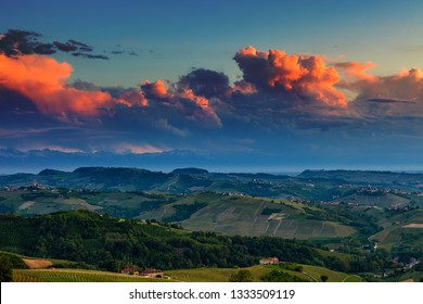 View from above on green hills with vineyards under beautiful evening sky in Piedmont, Northern Italy.